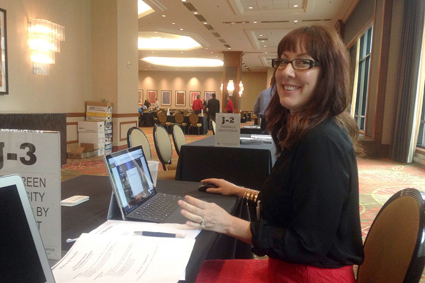 Director of Sales Kelley Shirazi sits at the BlueVolt table at the Evergreen Marketing Group's Power of Partnership Conference